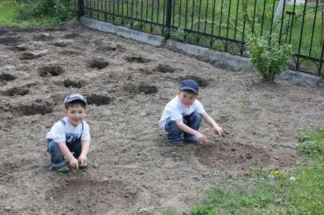 Two little farmers waiting for their squash to grow