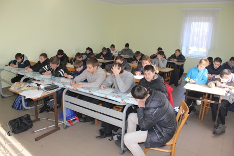 One of the fixed-up rooms. Notice insufficiant number of desks (some of them have bords instead of desk tops) and many boys being in their coats.