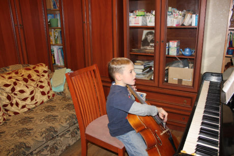 Our budding cellist in our crowded dining room
