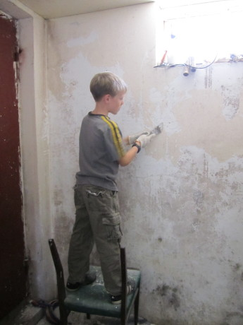 Yurko scraping off the wall to be plastered and painted